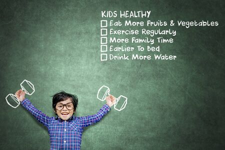 Happy little boy exercising with dumbbells while standing with lists of kids, healthy in chalkboard background