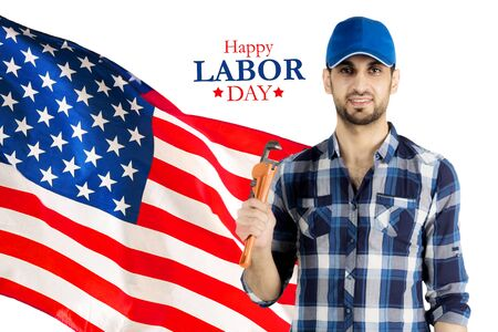 Male plumber holding a wrench while standing with an American flag and Happy Labor Day text in the studio Stok Fotoğraf