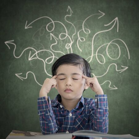 Picture of little boy thinking with eyes closed while sitting with arrow chaotic symbols over his head