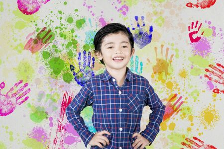 Picture of a cute little boy smiling at the camera while standing with colorful prints of hands background
