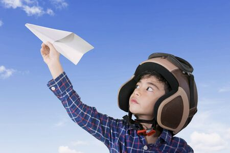 Picture of a little male pilot wearing helmet while playing a paper plane with blue sky background Stok Fotoğraf