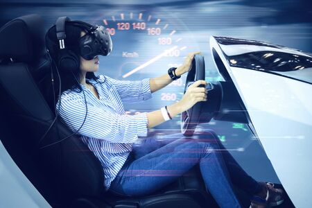 Side view of young woman using a VR glasses while driving a simulator car with a speedometer and fast motion blur