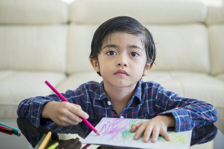 Asian little boy drawing with color pencils while sitting in the living room. Shot at home