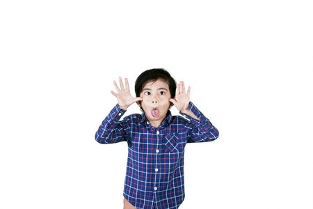 Picture of a little child mocking somebody with sticking out tongues at the camera, isolated on white