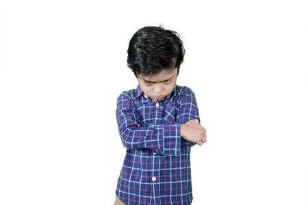 Picture of little boy crossed his arms while standing with cranky expression in the studio