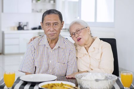 Picture of romantic elderly couple looking at the camera while having a meal together at the dining table