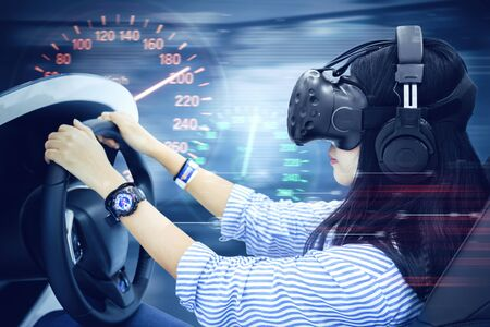 Young woman using a VR headset while playing on a racing simulator with a speedometer and fast motion blur Stok Fotoğraf