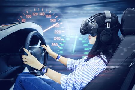 Close up of young woman using a VR glasses while driving a racing car with a speedometer and fast motion blur
