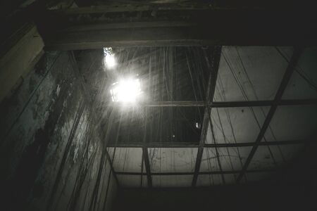 Image of sunlight entering through a rooftop of an abandoned house 스톡 콘텐츠