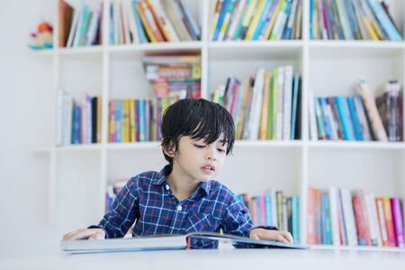 Picture of adorable little boy reading a book while studying in the library with bookcase