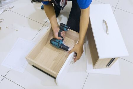 Close up of carpenter hands installing a drawer with a drill while installing a new cabinet furniture at home