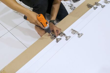 Hands of handyman mounting screws with a drill while installing a new cabinet furniture