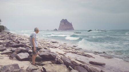 Rear view of old man standing on the Papuma coastline while enjoying seascape at misty morning 写真素材