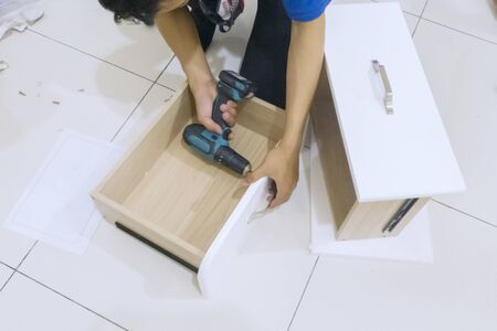 Close up of repairman hands assembling a new furniture with a drill at home Stockfoto