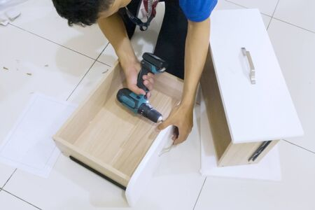 Close up of repairman assembling a drawer with a drill while installing a new cabinet furniture at home