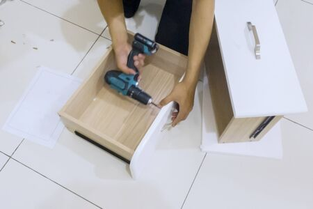 Hands of repairman assembling a drawer with a drill while installing a new cabinet furniture at home Stockfoto
