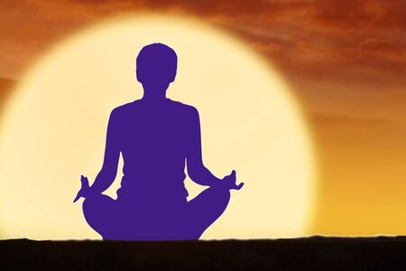 Young woman doing yoga exercises with indigo blue chakra at sunset time Stock fotó