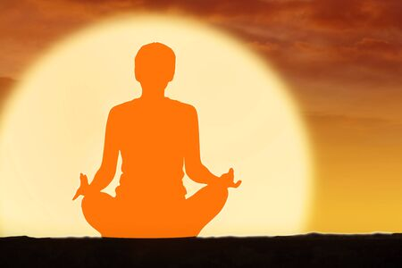 Picture of young woman doing yoga exercise while meditating with Svadhisthana chakra at sunset time