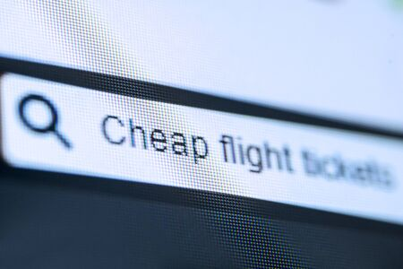 Concept of search engine. Close up of search bar with typed Cheap Flight Tickets text on the computer screen