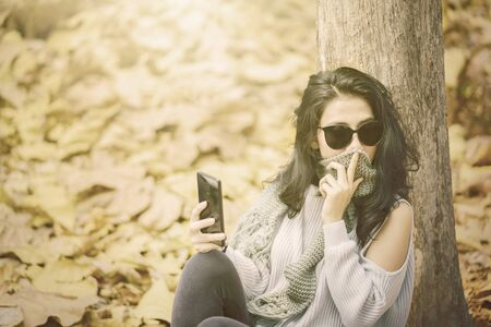 Young woman sitting at autumn park while holding a mobile phone and wearing sunglasses. Autumn Concept. Shot outdoors
