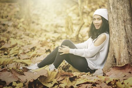 Attractive woman smiling at the camera while sitting at the autumn park and leaning on a tree. Autumn Concept. Shot outdoors 版權商用圖片