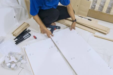 Close up of handyman assembling parts of a new piece of furniture at home Stockfoto