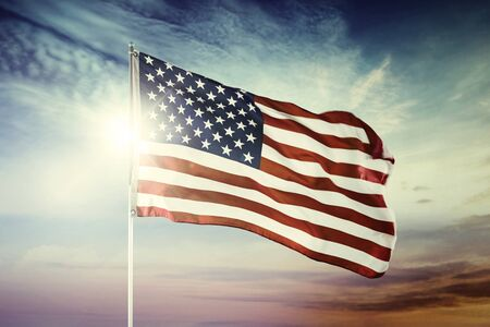 Image of American flag blowing in a wind with sunrise background at dawning time
