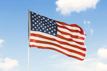 Image of American flag waving in a wind under blue sky