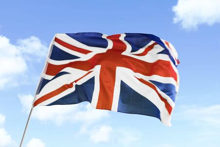 Image of United Kingdom flag waving in the wind with blue sky background