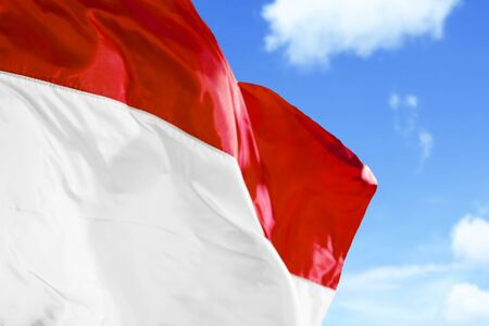 Close up of Indonesia flag waving in the air on a flagpole with blue sky background Stock Photo