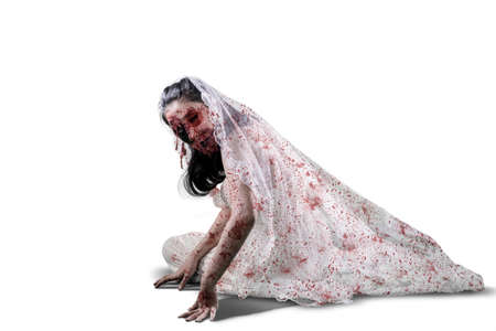 Halloween horror concept. Creepy female ghost wearing bride gown while crawling on the studio, isolated on white background Standard-Bild