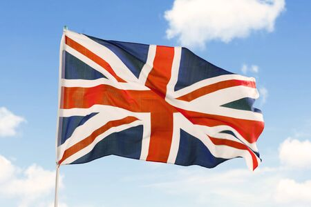 Image of United Kingdom flag blowing in the wind on a flagpole under blue sky