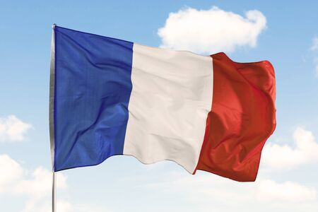 France flag waving in the wind on a flagpole under blue sky