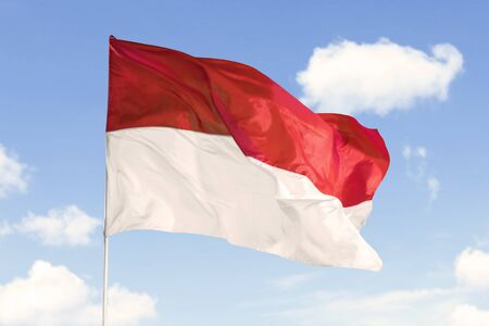 Indonesia flag waving in the air on a flagpole under blue sky