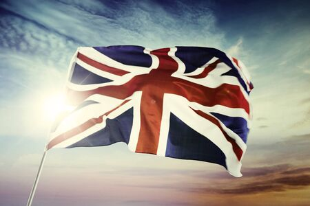Image of United Kingdom flag blowing in the wind with sunrise background Stock Photo