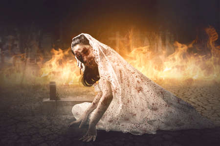 Halloween horror concept. Creepy female ghost wearing bride gown while crawling in the burning cemetery Standard-Bild