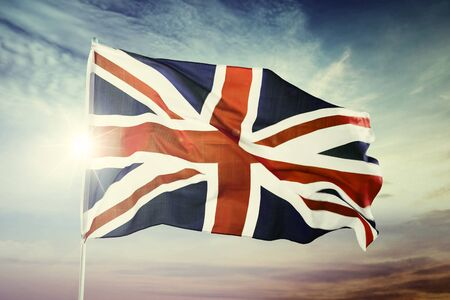 Image of United Kingdom flag waving in the sky at dawning time