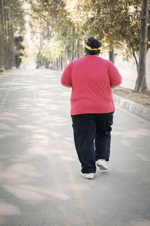 Rear view of a young fat man doing run exercises on the road at autumn time