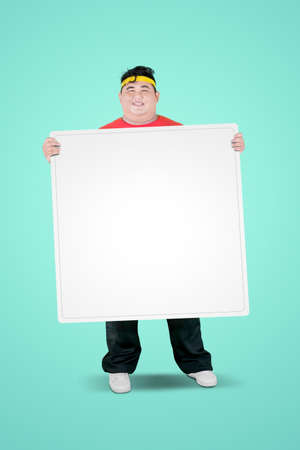 Portrait of an obese man wearing sportswear while holding a blank whiteboard in the studio