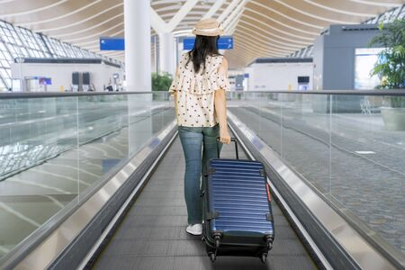 Rear view of young woman walking on the airport escalator while carrying her luggage
