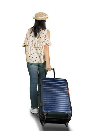 Rear view of young woman walking in the studio while pulling a luggage for traveling or holiday. Isolated on white background