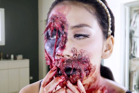Close up of young woman doing horror face makeup in the makeup room. Halloween day concept