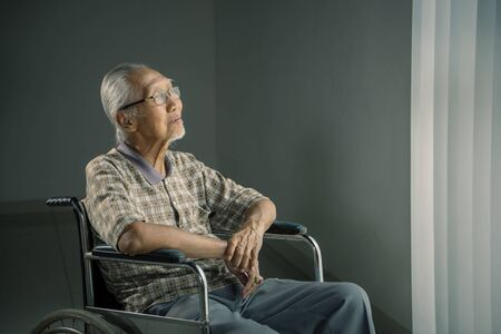 Picture of smiling old man sits in the wheelchair while thinking something in the retirement home 写真素材