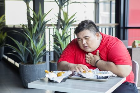 Obese person looks getting heart attack while eating junk foods in the restaurant. Unhealthy lifestyle concept.