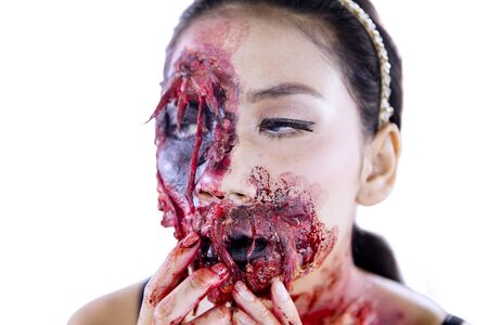 Close up of a horrible female zombie with wounds on her face, isolated on white background