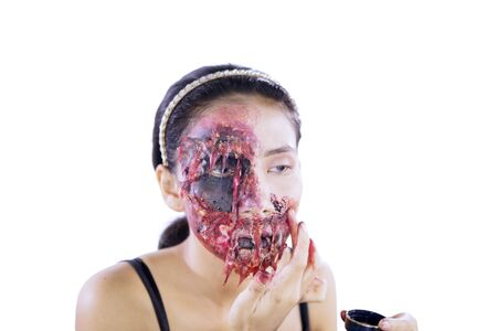 Halloween day concept. Young woman applying fake blood makeup on her face, isolated on white background
