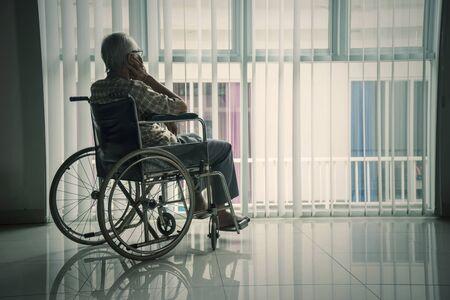 Rückansicht eines älteren Mannes, der im Rollstuhl sitzt und aus dem Fenster im Altersheim schaut Standard-Bild