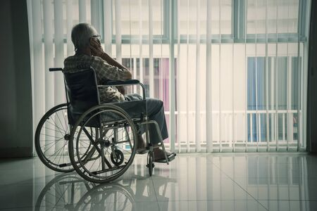 Rear view of a senior man sitting in the wheelchair while looking out the window in the retirement home Stock fotó