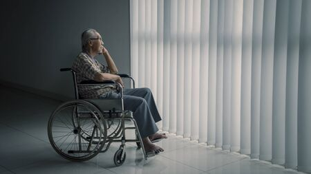 Picture of senior man sitting in the wheelchair while looking out the window in the retirement home 写真素材