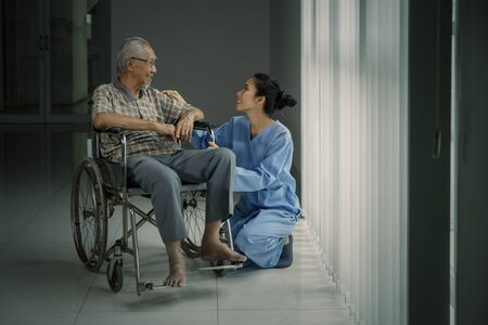 Picture of elderly man talking with his nurse while sitting in a wheelchair near the window